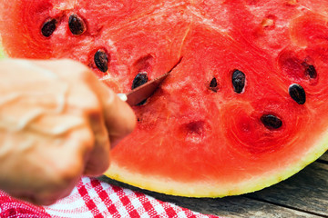 Close up knife cutting slice of watermelon