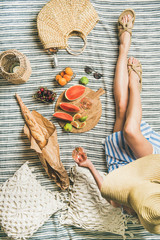 Aluminium Prints Picnic Summer picnic setting. Young woman in striped dress and straw sunhat sitting with glass of rose wine in hand, fresh fruit on board and baguette on blanket, top view. Outdoor gathering or lunch concept