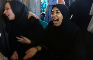 Relatives of Palestinian medic Abdullah Al-Kotati, who was killed while trying to help wounded protesters at the Israel-Gaza border, mourn during his funeral in Rafah in the southern Gaza Strip