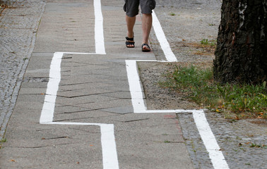 A man walks on a bike lane, after the lane marking was restored recently in a strange zigzag shape at Zehlendorf district in Berlin