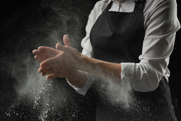 Cook hands in flour on black background banner. Making pizza, pasta, baking bread and sweets.