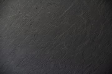 Schwarze Anthrazitplatte mit rauen Konturen als Hintergrund oder Untergrund