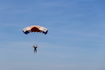 isolated skydiver in colorful parachute gliding after free fall jump with blue sky background