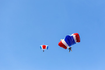 skydiver team in colorful parachute gliding after free fall jump with blue sky background