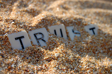 Letters of word 'trust' being buried in sand