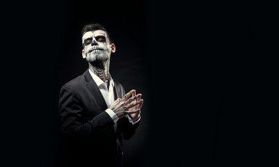Portrait of man with Halloween skull makeup on the black background.