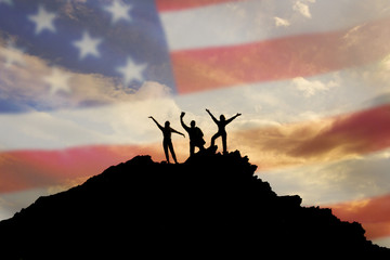 Silhouettes of happy three people on top of a mountain, but the background of the flag of the America and sky.