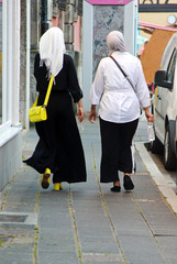 rear view of two young moslem women with walking side by side