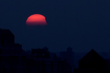 A partial eclipse of the sun, as it sets, is seen from Shanghai