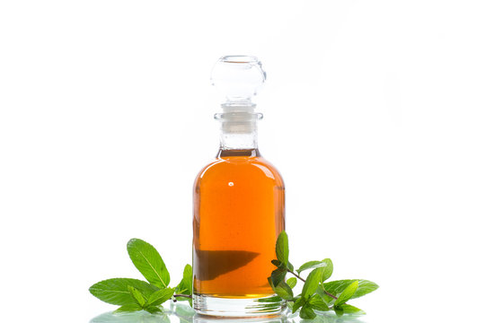 Mint syrup in a glass bottle on a white background