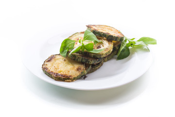 Fried zucchini in a white plate isolated