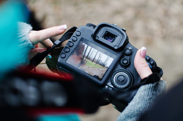 girl is looking at the frame on the camera screen. A girl photographer with a French manicure in a park in the fall.