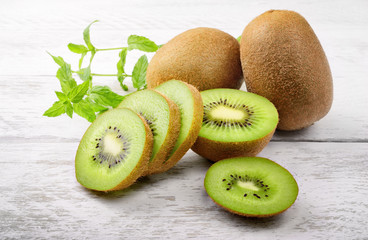 Green kiwi and mint leaves on white wood background