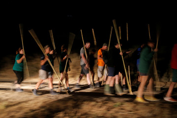 Volunteers hold canes before wading across the lagoon at dawn to gather flamingo chicks and place them inside a corral in the Fuente de Piedra natural reserve near Malaga