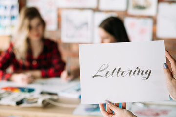 lettering art and calligraphy craft. italic cursive handwriting courses. woman hands holding paper with text. creative leisure and artistic hobby.