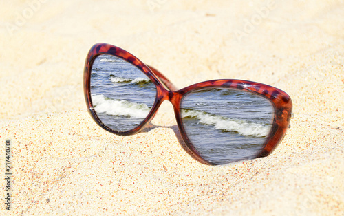 Sunglasses are on sand. The image of the sea is in a frame of ...