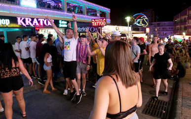 Tourists walk shouting at Punta Ballena street in Magaluf