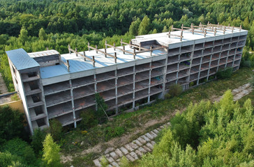Old destroyed and ruined industrial building in forest, aerial view