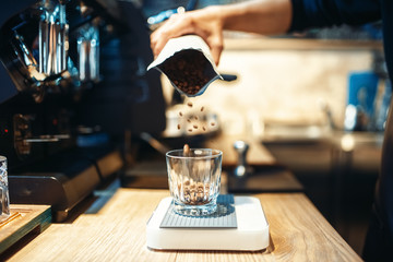Barista hand pours coffee beans into the glass