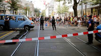 Revellers walk past Swiss police officers on their way to the Street Parade dance music event in Zurich