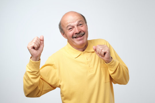 Mature happy man moving dancing over white background.