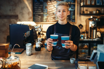 Male barista holds two cups of fresh hot coffee