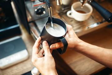 Male barista prepares beverage on coffee machine