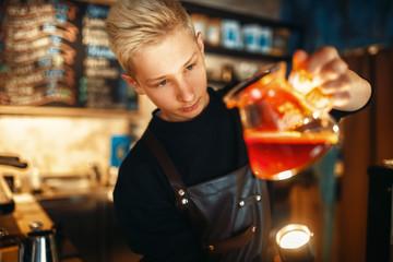 Male barista checks the sediment in the coffee pot