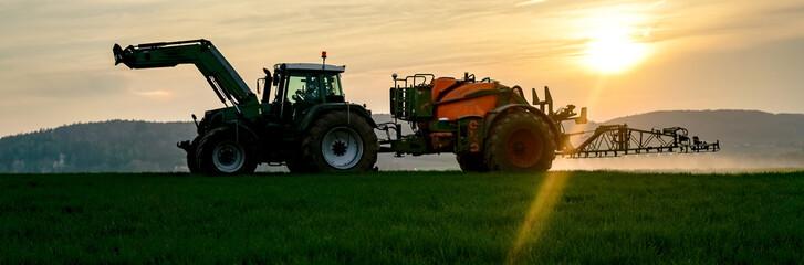 Landwirt mit Feldspritze am Abend im Getreidefeld beim Spritzen, Gegenlicht - Bild im Bannerformat Fototapete