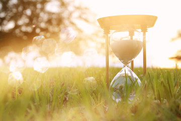 Hourglass in the grass time during sunset. vintage style.