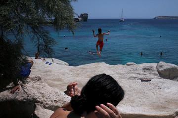 A boy jumps into the sea from a rock on Karas beach on the island of Kimolos