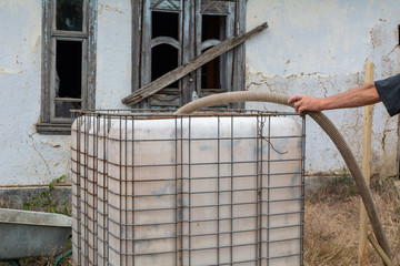 A man fills a plastic tank with water