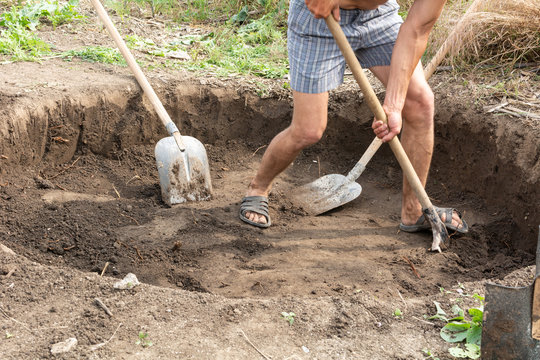 Workers dig a pit for a septic tank in a private house