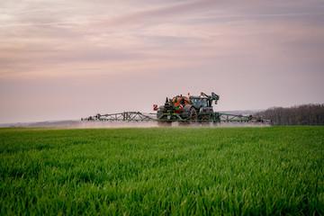 Ackerbau - Landwirt spritzt nach Feierabend sein Getreide gegen Unkraut