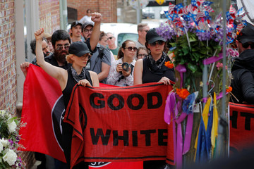 "A group wearing anti-fascist labels visits the site where Heather Heyer was killed during the 2017 Charlottesville ""Unite the Right"" protests in Charlottesville"