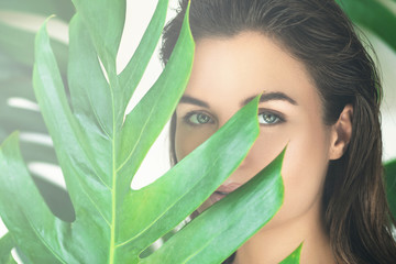 Portrait of young and beautiful woman with perfect smooth skin in tropical leaves.