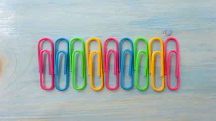 Colored Paper Clips on Light Blue Wood. Photo Image