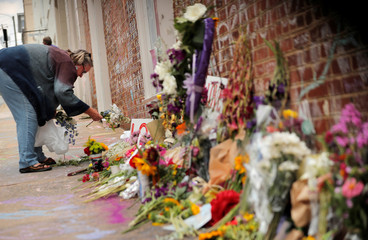 "A woman places flowers at a memorial near the site where Heather Heyer was killed during the 2017 Charlottesville ""Unite the Right"" protests in Charlottesville"