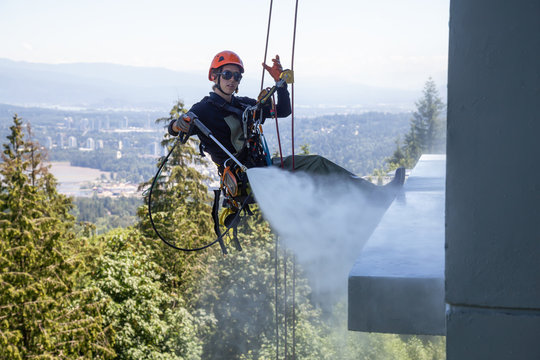 High rise rope access window cleaner is power washing the building during a hot sunny summer day. Taken in Burnaby Mountain, Vancouver, BC, Canada.