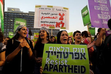 Israeli Arabs and their supporters take part in a rally to protest against Jewish nation-state law in Rabin square in Tel Aviv