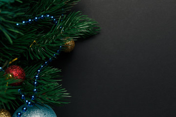 Christmas or New Year decoration background: fur-tree branches, colorful glass balls on black grunge background. Christmas composition. Flat lay. Top view. Copy space. Christmas decorations