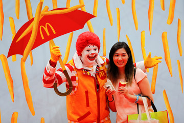 An attendee poses for a picture with McDonald's mascot Ronald McDonald at KCON USA, billed as the world's largest Korean culture convention and music festival, in Los Angeles