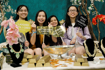 """Attendees pose for a picture at a booth promoting the new movie """"Crazy Rich Asians"""" as they participate at KCON USA, billed as the world's largest Korean culture convention and music festival, in Los Angeles"""