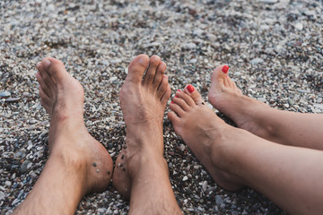 women and men feet in the sea on a sandy beach