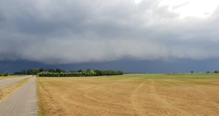wall cloud of a thunderstorm above dry yellow fields and green trees in Laag Zuthem in Overijssel, the Netherlands