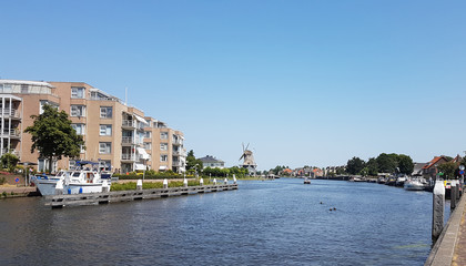 River Vliet in Leidschendam with blue sky and windmill Salamander on the background in the Netherlands.