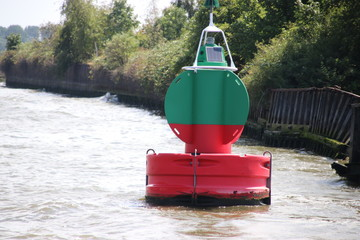 Red green buoy in the waterway marking that both sides can be used in river Noord in The Netherlands.
