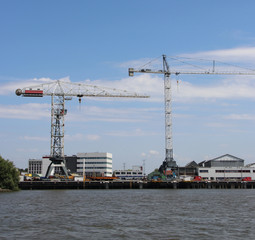Docks with ships and cranes along the riverside of the river Lek or Noord in the Netherlands