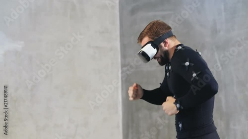 athletic bearded man in motion capture suit having fun in