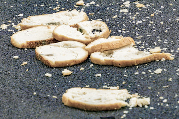 A lot of bread is lying on the asphalt, spoiled bread, hunger